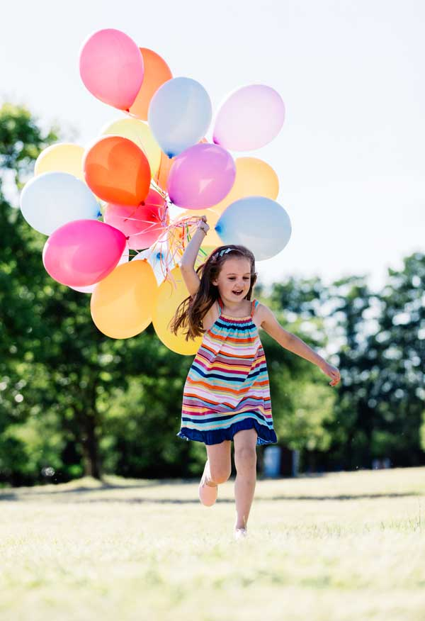 Happy girl running with balloons